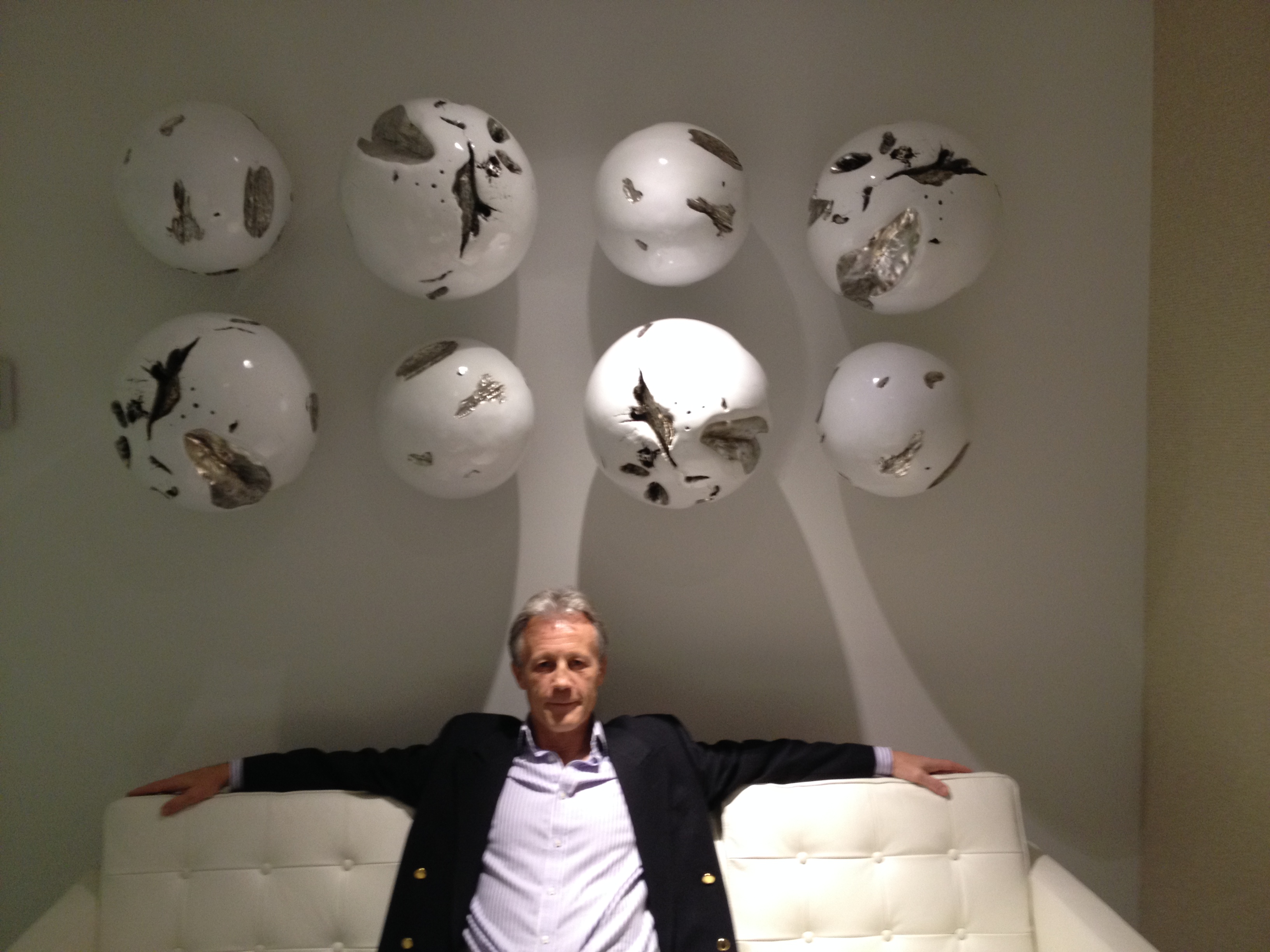 PR Smith, author, sitting on couch with footballs on the wall